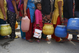 Girl stands in a queue to fill her container with water near the makeshift shelters after Saturday's earthquake in Kathmandu